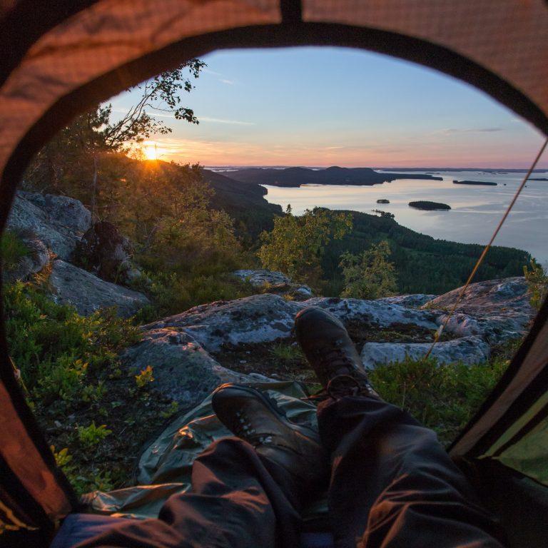 retkeilijä katselee auringonlaskua teltasta